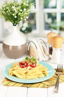 Rigatoni pastaschotel met tomatensaus op witte houten tafel in café