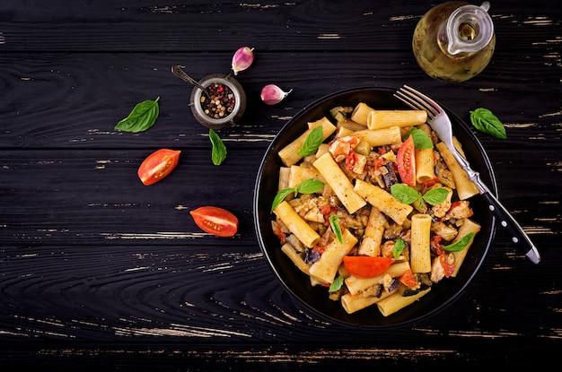 Rigatonideegwaren met kippenvlees, aubergine in tomatensaus in kom. italiaanse keuken. bovenaanzicht kopieer ruimte