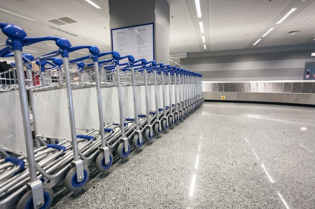 Rij bagagekarretjes bij aankomstterminal op luchthaven
