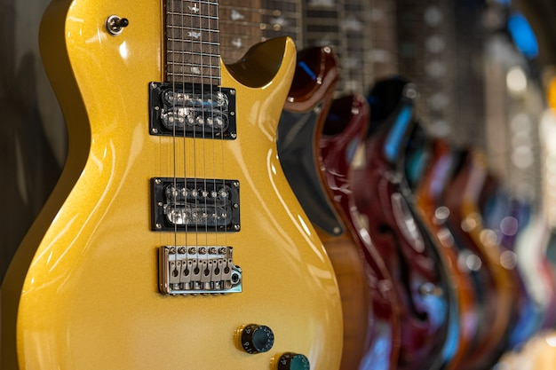 Rij elektrische gitaren in verschillende kleuren in een winkel met muziekinstrumenten