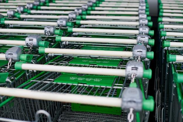 Rij geparkeerde karren in supermarkt. veel lege groene winkelwagentjes in rij.
