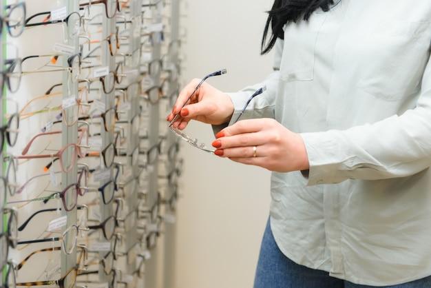 Rij glazen bij een opticien. brillen winkel. staan met een bril in de winkel van optica. de hand van de vrouw kiest een bril. gezichtscorrectie.