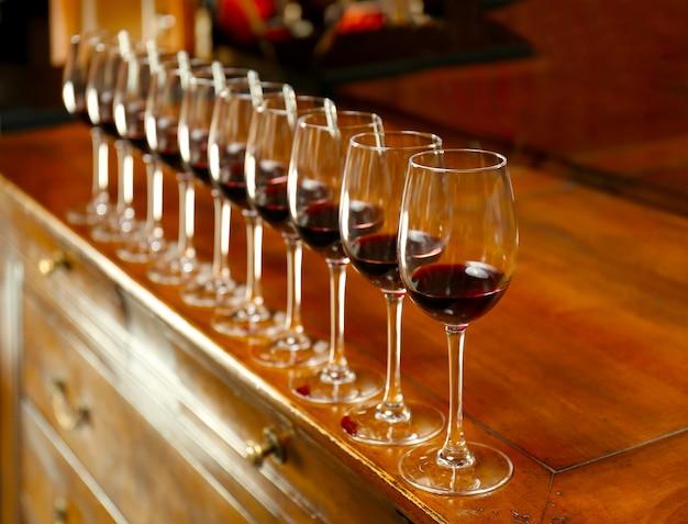 Rij glazen met rode wijn op toog