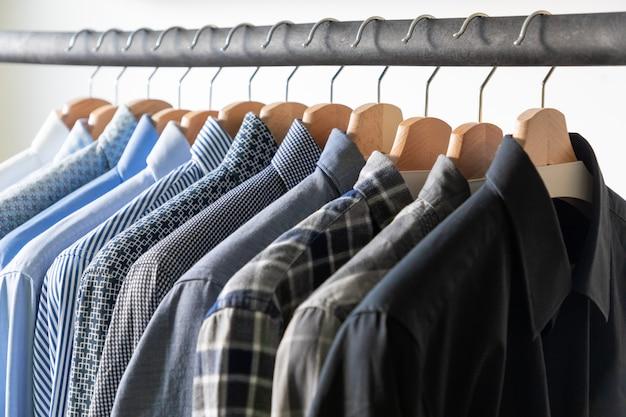 Rij heren overhemden in blauwe kleuren op hanger