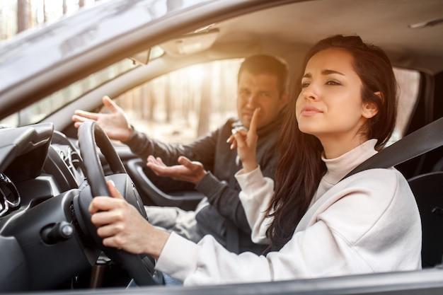 Rij-instructie. een jonge vrouw leert autorijden. haar instructeur of vriend houdt niet van de manier waarop ze autorijdt. maar het meisje is tevreden over zichzelf en luistert niet naar de man.