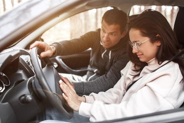 Rij-instructie. een jonge vrouw leert voor het eerst een auto te besturen. ze werkt niet goed. haar man of instructeur schreeuwt tegen haar. ze is aan het huilen