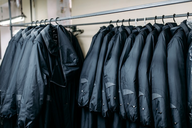 Rij jassen op een hangers, kledingwinkel, naaifabriek of kledingstof. kleren op rekken