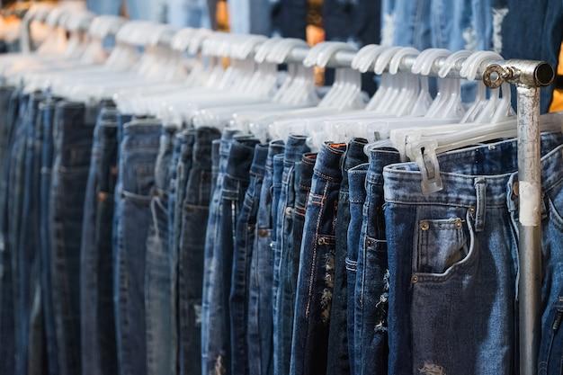 Rij jeans en broek op hangers te koop.