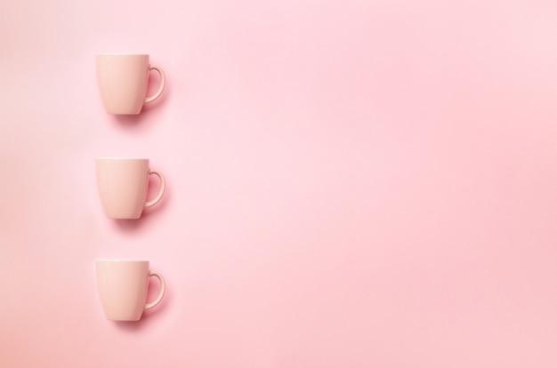 Rij met roze kopjes op pittige achtergrond. verjaardagspartij, babydouche concept. minimalistisch stijlontwerp