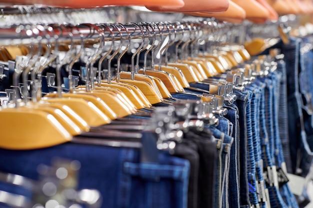 Rij opgehangen blauwe en zwarte jeans op houten hangers in de winkel. veel jeans hangen aan het rek. rij broek denim jeans hangen in de kast. concept van kopen, verkopen, winkelen en jeansmode.