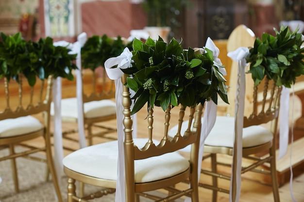 Rij stoelen versierd met groene bladeren en witte linten voor huwelijksceremonie
