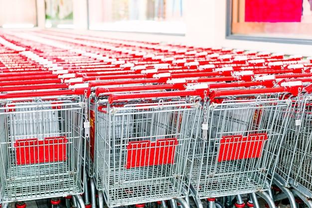 Rij van boodschappenwagentjes met rode handvatten op avond onscherpe achtergrond dichtbij ingang van supermarkt in de winter