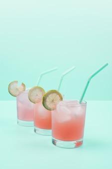 Rij van cocktailglazen met ijsblokjes; rietje; plakjes citroen op munt achtergrond