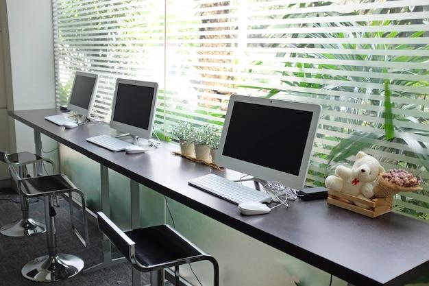 Rij van computers die op mensengebruik wachten bij internetcafé.