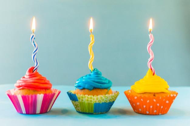 Rij van cupcakes met brandende kaarsen op blauwe achtergrond