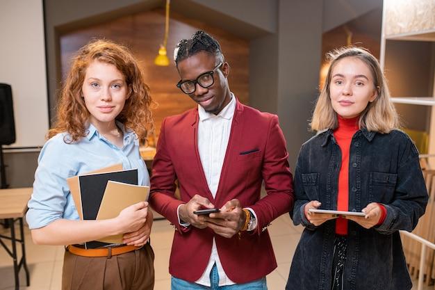 Rij van drie succesvolle hedendaagse multiculturele studenten van de universiteit of middelbare school die naar je kijken in café