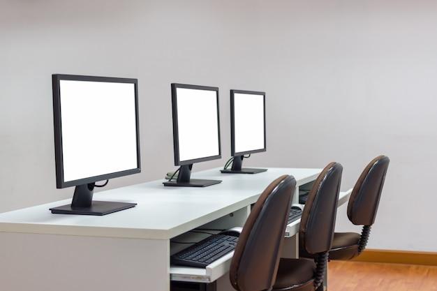 Rij van drie witte schermmonitors op bureau met toetsenbord. selectieve nadruk beeld met exemplaar s