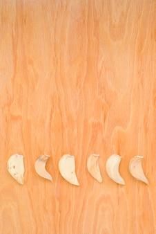 Rij van droge garlics in verticale foto op houten achtergrond