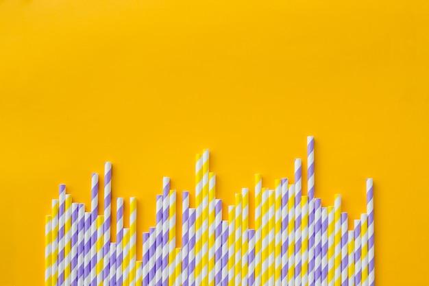 Rij van elegant wit gestreept papier rietjes op gele achtergrond. verjaardagspartij babyshower uitnodigingskaart fun kids vakantie viering concept. minimalistische stijl. kopie ruimte