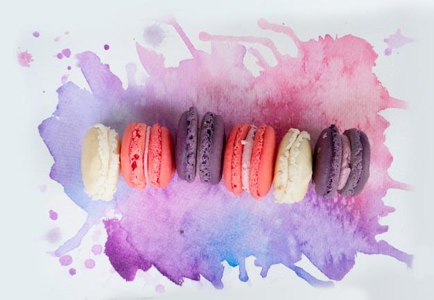 Rij van franse koekjes bitterkoekjes op aquarel achtergrond, bovenaanzicht
