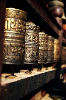 Rij van gebedsmolen gemaakt van metaal in de tempel in nepal