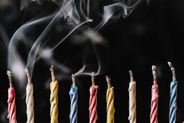 Rij van gedoofde kaarsen gerangschikt op zwarte achtergrond