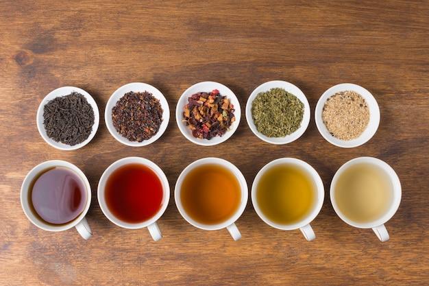 Rij van gedroogde kruiden met aroma witte thee kopjes op houten tafel