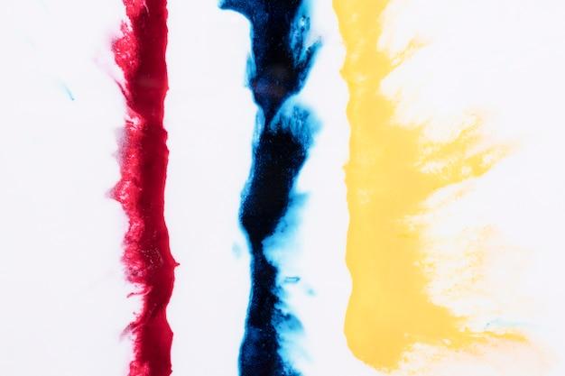 Rij van geel; blauwe en rode kleurenplons die over witte achtergrond wordt geïsoleerd