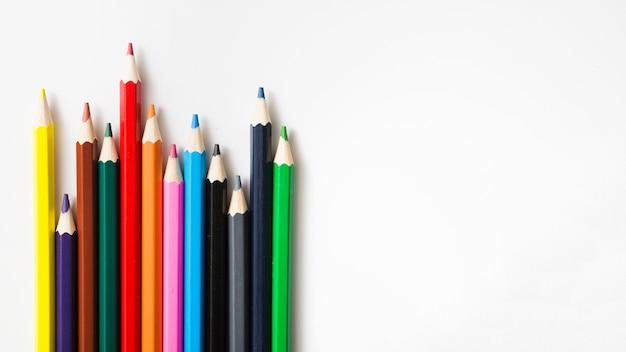 Rij van gekleurde scherpe potloden tegen witte achtergrond