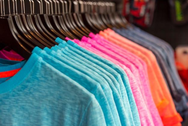 Rij van gekleurde t-shirts in een winkel