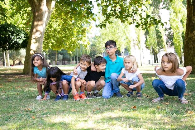 Rij van gelukkige kinderen doen samen squats in park, knuffelen elkaar, wegkijken in opwinding. kinderfeestje of entertainment concept