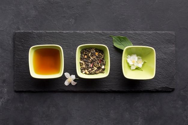 Rij van gezond theeingrediënt en witte jasmijnbloem op leisteen