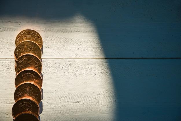 Rij van gouden munten aan boord en zonneschijn in de duisternis