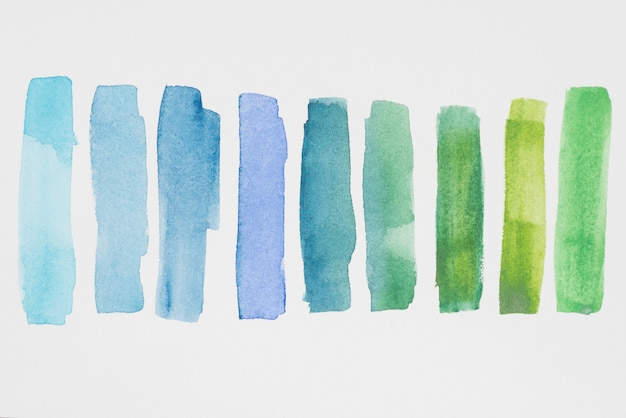Rij van groene en blauwe verven op wit papier