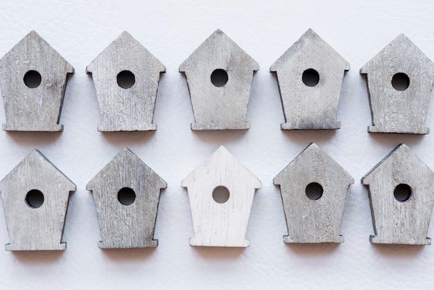 Rij van houten vogelhuizen op witte geweven achtergrond
