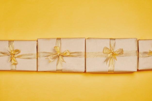 Rij van huidige dozen van kerstmis op gele achtergrond. kerstcadeaus verpakt op ambachtelijk papier en vastgebonden met gouden lint