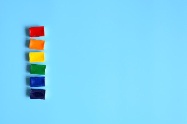 Rij van individuele pallets met aquarellen van regenboogkleuren op een blauwe achtergrond. ruimte voor tekst