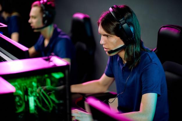 Rij van jonge hedendaagse exploitanten met hoofdtelefoons die in fauteuils voor computermonitors in call centre zitten en cliënten raadplegen