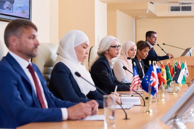 Rij van jonge interculturele afgevaardigden in formalwear zittend aan tafel microfoons op conferentie