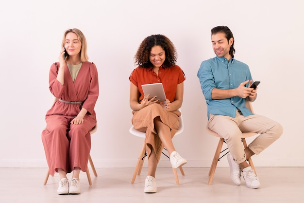 Rij van jonge interculturele vrienden in vrijetijdskleding die langs de witte muur zitten en communiceren via smartphones en touchpad