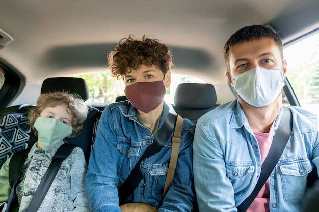 Rij van jonge man en vrouw en hun schattige zoontje in spijkerjasjes en beschermende maskers zittend op de achterbank van de auto