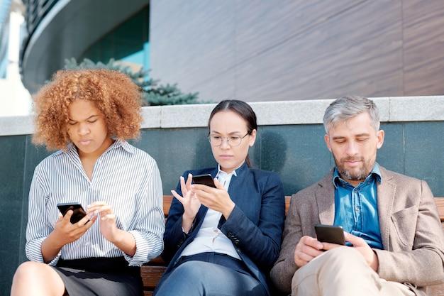 Rij van jonge mobiele werknemers zittend op een bankje langs de muur en scrollen in hun smartphones na het werk