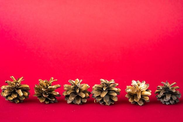 Rij van kerstboomkegels op rood
