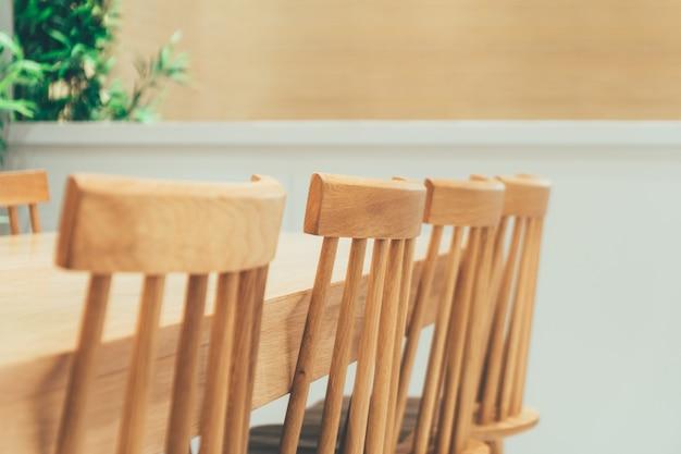 Rij van klassieke en gezellige natuurlijke houten windsor stoelen en eettafel in mooie, minimalistische design kamer met planten.