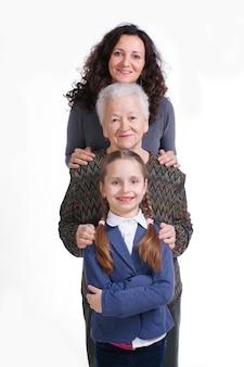 Rij van klein meisje, grootmoeder, moeder die camera in lijn op een witte achtergrond bekijkt