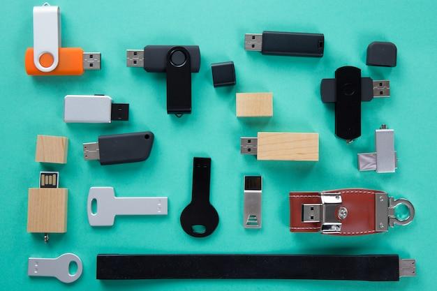 Rij van kleuren usb flash drives op groene tafel, bovenaanzicht