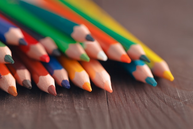 Rij van kleurenpotloden op houten lijst