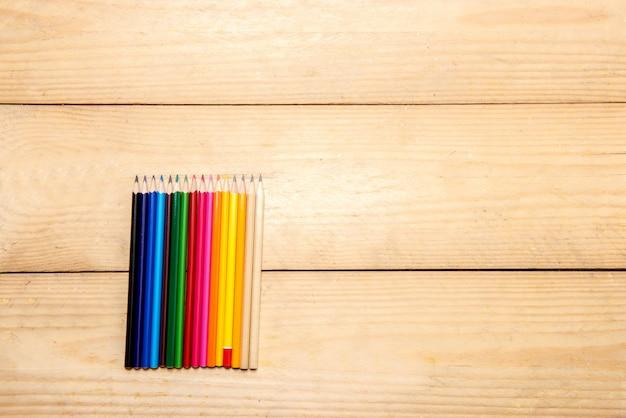 Rij van kleurrijke kantoorbehoeften van potloden voor het trekken op de houten lijst