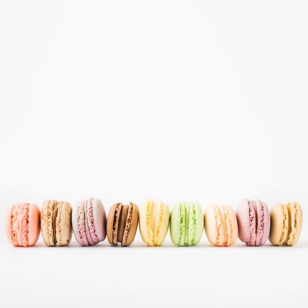 Rij van kleurrijke makarons die op witte achtergrond wordt geïsoleerd
