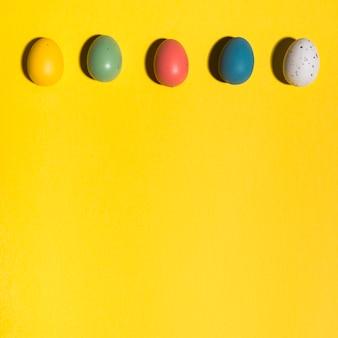 Rij van kleurrijke paaseieren op gele lijst